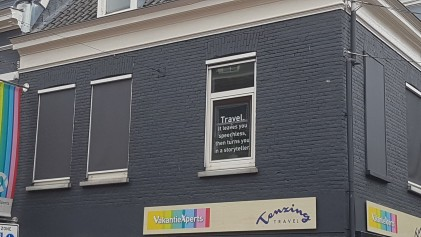 "An inspiring message on one of the windows in the centre of Nijmegen: ""Travel. It leaves you speechless, then turns you in a storyteller."""